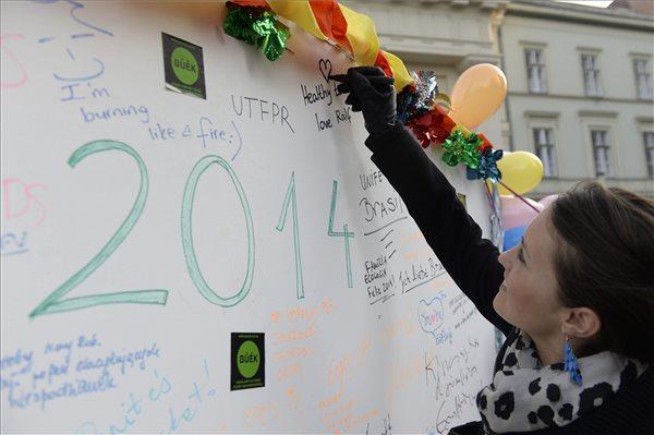 Egy nő újévi kívánságait írja egy üzenőfalra a BÚÉK című közösségi dokumentumfilm csapatának utcai akcióján a budapesti Deák téren, 2013. december 29-én. A film bemutatóját 2014 decemberére tervezik az alkotók. MTI Fotó: Bruzák Noémi