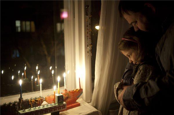Radnóti Zoltán neológ rabbi és kislánya, Mirjam nézik a hanukiákban égő gyertyákat a nyolcnapos zsidó vallási ünnep, hanuka első estéjén 2013. november 27-én. MTI Fotó: Kallos Bea