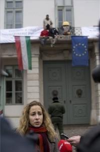 Budapest, 2014. február 9. Szabó Rebeka, az Együtt-PM politikusa nyilatkozik a sajtónak a Sándor-palota előtt 2014. február 9-én, ahol a párt három aktivistája (a háttérben) transzparensekkel népszavazást követelt a paksi bővítésről. MTI Fotó: Kallos Bea