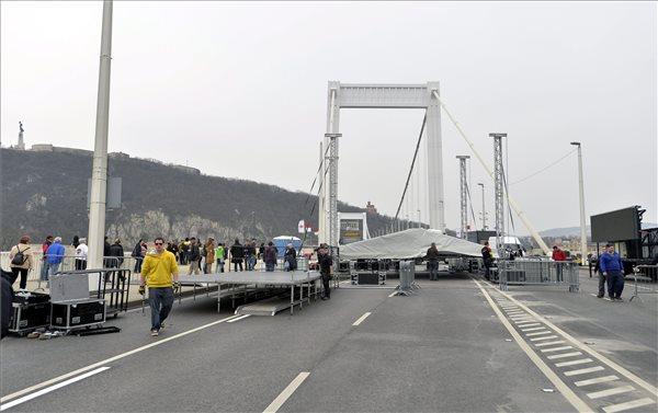 Bontják a színpadot az Erzsébet híd pesti hídfőjénél, miután bejelentették, hogy a várható vihar és az erős szél miatt elmarad az ellenzéki összefogás délutáni tüntetése 2014. március 15-én. MTI Fotó: Máthé Zoltán