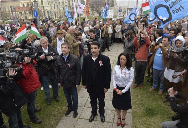 Bajnai Gordon, az Együtt-PM vezetője, Mesterházy Attila, a Magyar Szocialista Párt (MSZP) elnöke és Szabó Tímea, a Párbeszéd Magyarországért (PM) társelnöke (középen, b-j) szimpatizánsok között Budapesten, a Petőfi téren, miután bejelentették, hogy a várható vihar és az erős szél miatt elmarad az ellenzéki összefogás délutáni tüntetése 2014. március 15-én. MTI Fotó: Máthé Zoltán