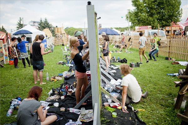 Fesztiválozók festenek a berlini fal lebontásának 25. évfordulója alkalmából ajtókból épült falinstallációra a budapesti Sziget fesztiválon 2014. augusztus 15-én. MTI Fotó: Marjai János