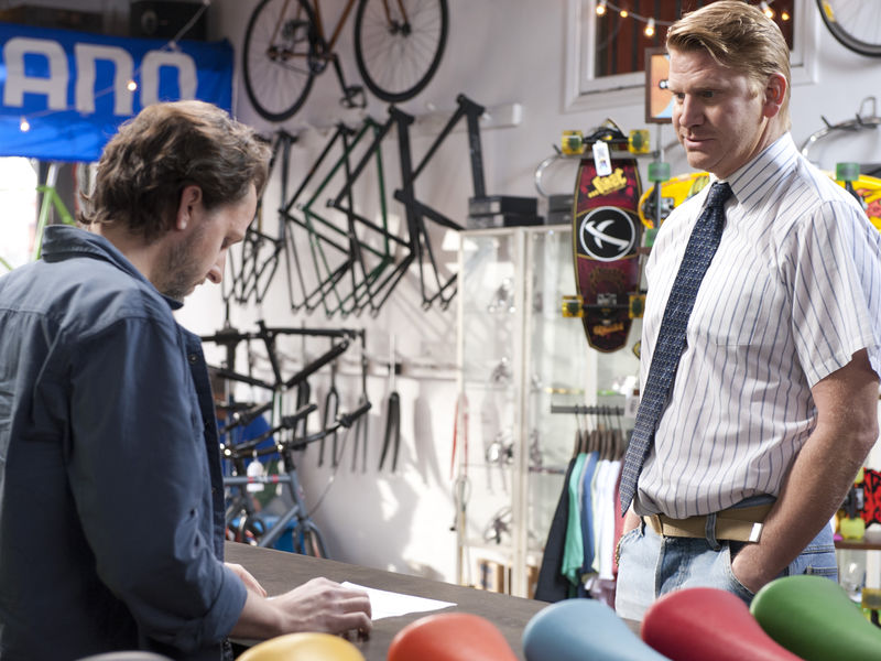 James Thomas Gilbert at the Bike Store Manager and Dash Mihok as Bunchy Donovan in Ray Donovan (Season 2, Episode 1). - Photo:  Suzanne Tenner/SHOWTIME - Photo ID:  RayDonovan_201_0838.R