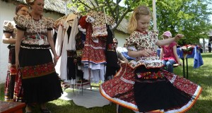gy kislány felpróbál egy ruhát a mezőkövesdi Matyó Népművészeti Egyesület bemutatóján, a Pünkösdi Örökség Fesztiválon a szentendrei Szabadtéri Néprajzi Múzeumban 2015. május 24-én. MTI Fotó: Bruzák Noémi