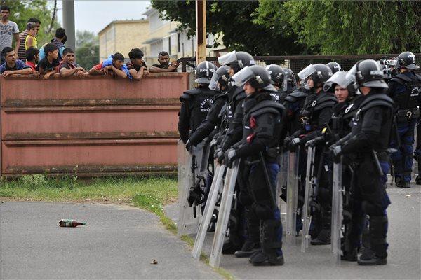 Rendőrök állnak készenlétben a debreceni migrációs tábor bejáratánál 2015. június 29-én. A környékbeliek elmondása szerint a tábor mintegy száz lakója autókat rongált meg és kukákat gyújtott fel. A táborlakók kiabáltak a kiérkező rendőrök felé. A Hajdú-Bihar Megyei Rendőr-főkapitányság közlése két menedékkérő között vallási indíttatású nézeteltérés alakult ki a Bevándorlási és Állampolgársági Hivatal debreceni befogadóállomásán. A konfliktus elmérgesedett, abba az állomáson tartózkodó menedékkérelmet benyújtók közül több százan kapcsolódtak be. MTI Fotó: Czeglédi Zsolt