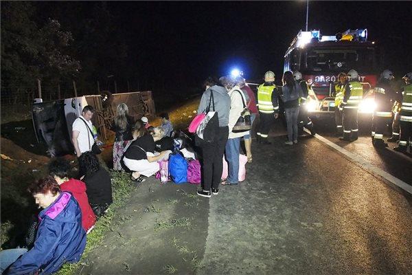 Utasok ülnek egy oldalára dőlt autóbusz mellett az M5-ös autópályán 2015. július 14-én hajnalban. Az egyik nemzetközi társaság Salzburgból Bulgáriába tartó autóbusza a 133-as kilométer közelében, a Szeged felé vezető oldalon árokba hajtott és felborult. A mentők a helyszínről huszonegy embert szállítottak kórházba, hét embert súlyos, egyiküket életveszélyes sérülésekkel. MTI Fotó: Donka Ferenc