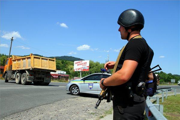 Fegyveres rendőr és úttorlaszként használt teherautó Munkács határában, a Csap-Kijev főútvonalon, az előző napi lövöldözés helyszínén 2015. július 12-én. Július 11-én tűzharc tört ki Munkácson egy sportlétesítménynél a Jobboldali Szektor (PSZ) szélsőséges szervezet fegyveresei és az ukrán parlament egyik kárpátaljai képviselőjének emberei, valamint a helyszínre érkező rendőrök között. A lövöldözésben, amely másfél óra után az autóúton folytatódott, a PSZ sajtószolgálata szerint a szervezet két tagja életét vesztette, négy másik pedig megsebesült. MTI Fotó: Nemes János