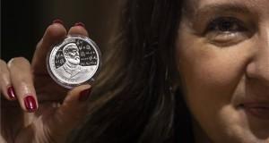 A Magyar Nemzeti Bank által kibocsájtott emlékérmet mutatja egy nő az Eötvös Loránd fizikus halálának 100. évfordulója alkalmából rendezett ünnepségen az MTA dísztermében 2019. április 8-án. MTI/Szigetváry Zsolt