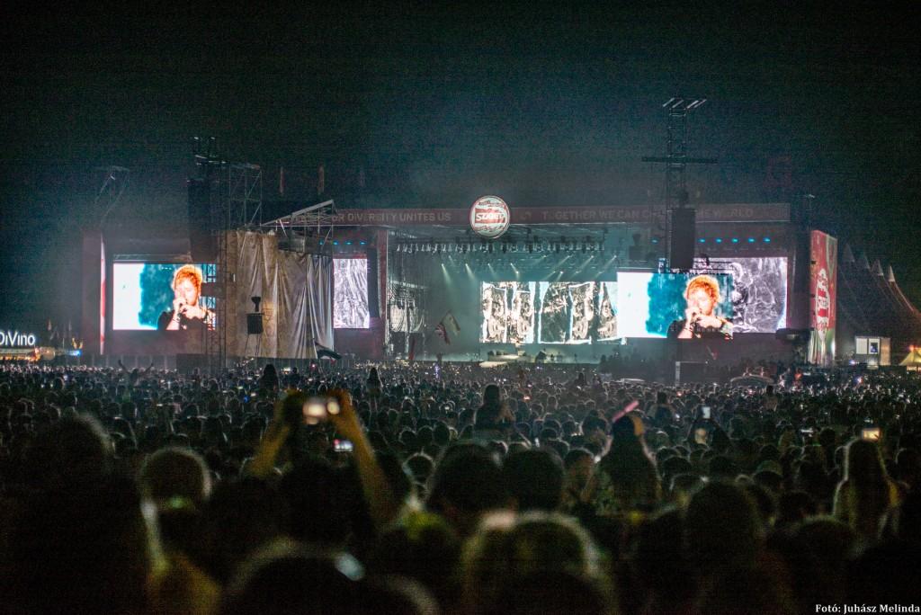 Ed Sheeran, a 28 éves brit zenész, dalszerző, énekes koncertjét hatvanezren nézték a Sziget Fesztivál nyitónapján.  Az elmúlt tíz évben több mint száz zenei díjat kapott, köztük négy Grammyt, számait pedig többmilliárdszor nézték meg a legnagyobb videomegosztón. A Shape of You című felvételét egyedül csaknem négymilliárdszor. Tavaly ő volt a világon a legtöbb eladást produkáló zenész. Fotó: Juhász Melinda