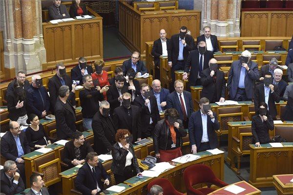 A DK, az MSZP és Párbeszéd képviselői (b-j) a kulturális törvénycsomag szavazása közben tiltakozásul felállnak és fekete maszkot tartanak az arcuk elé az Országgyűlés plenáris ülésén 2019. december 11-én. A parlament 115 igen, 53 nem és 3 tartózkodó szavazattal jóvá hagyta a kormány kulturális törvénycsomagját, amely állami, önkormányzati és közös fenntartású színházak létrejöttét teszi lehetővé. MTI/Bruzák Noémi